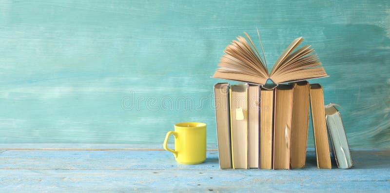Open boek op een rij van oude boeken en een kop van koffie Het lezen, het leren, onderwijs, literatuuronderwerpen royalty-vrije stock afbeelding