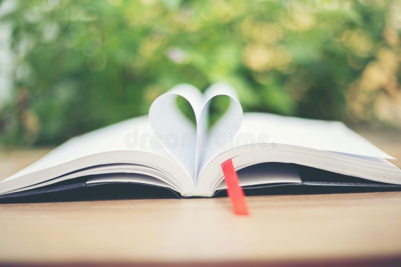 Open boek op houten lijst aangaande natuurlijke achtergrond De pagina van het hartboek stock afbeeldingen