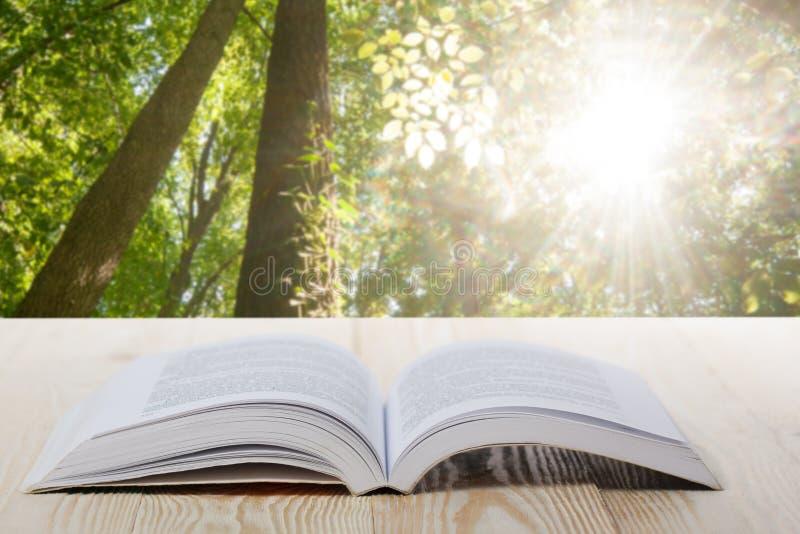 Open boek op houten lijst aangaande natuurlijke vage achtergrond Terug naar School De ruimte van het exemplaar royalty-vrije stock foto's