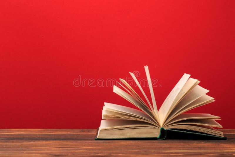 open boek op rode achtergrond Tekstplaats stock afbeelding