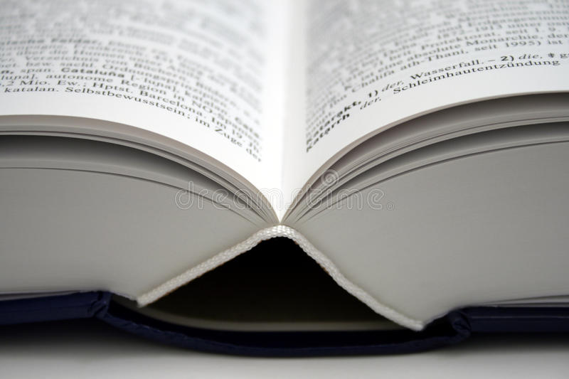 Open book. An opened word dictionary, shot from an angle that shows off the bowed pages, the center and binder part stock photo