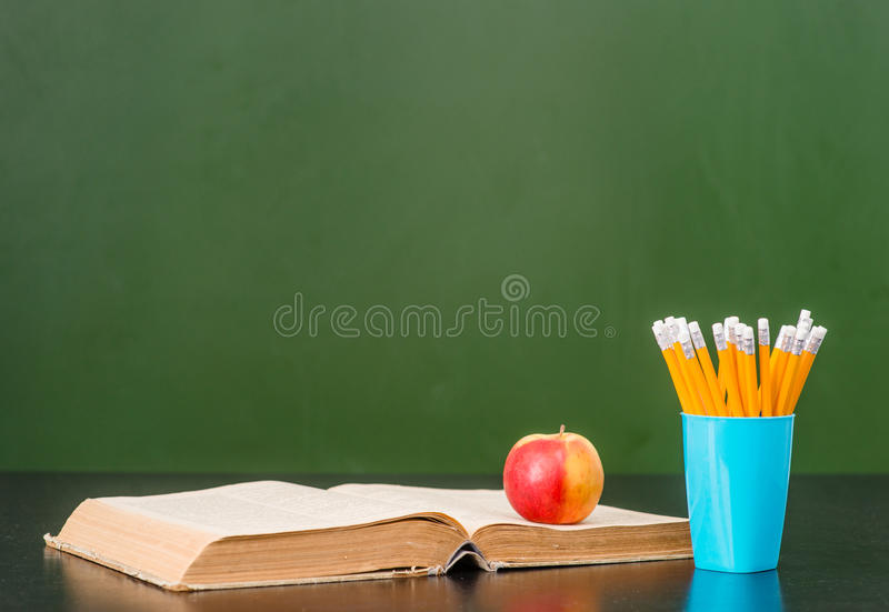 Open book with apple and pencils near empty green chalkboard. Sample for text stock photography