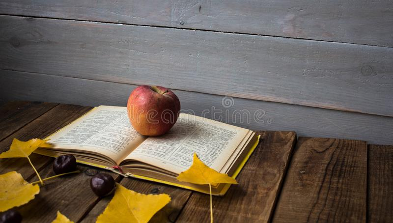A open book apple yellow leaves chestnut on wooden background royalty free stock photos