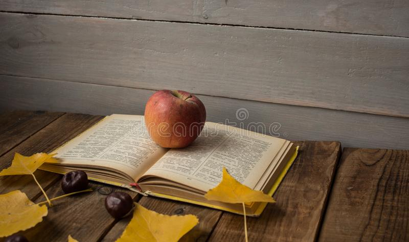 A open book apple yellow leaves chestnut on wooden background stock photo