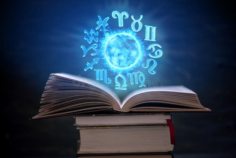 Open book on astrology on a dark background. The glowing magical globe with signs of the zodiac in the blue light. Concept of prediction and magic stock photo