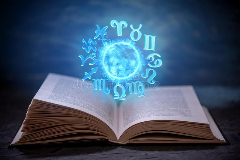 Open book on astrology on a dark background. Glowing magical globe with signs of the zodiac in the blue light. Open book on astrology on a dark background. The royalty free stock photos