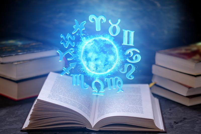 Open book on astrology on a dark background. Glowing magical globe with signs of the zodiac in the blue light. Open book on astrology on a dark background. The royalty free stock photo