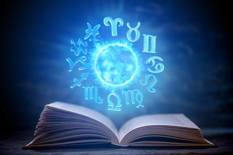 Open book on astrology on a dark background. Glowing magical globe with signs of the zodiac in the blue light. Open book on astrology on a dark background. The royalty free stock images