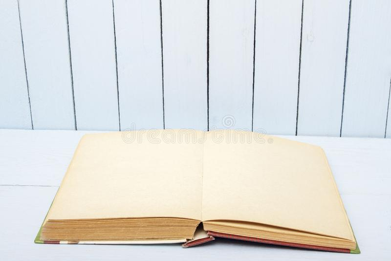Open book on background woodens table and wall. Blank pages fo copy space or text stock image
