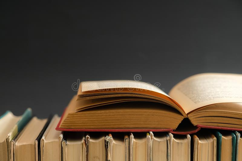 Open book on black background, hardback books on wooden table. E. Ducation and learning background. Back to school, studying. Copy space for text stock photos