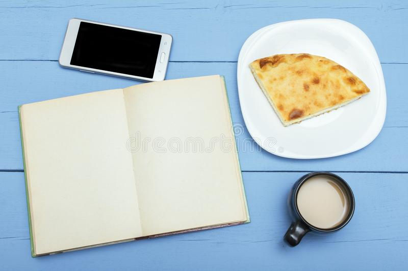 Open book with blank pages, tea or coffee with pie. Top view . royalty free stock photography