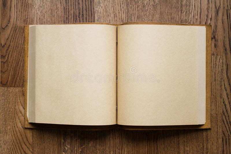 Open book with blank pages on wooden floor. Top view closeup of open book with leather covers and empty white pages on brown wooden parquet floor background stock photos