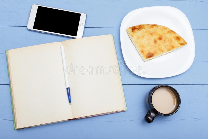 Open book with blank pages on wooden table for design or copy space, tea or coffee with milk and pie. Top view . stock photography