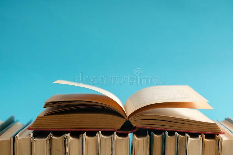 Open book on blue background, hardback books on wooden table. Ed. Ucation and learning background. Back to school, studying. Copy space for text stock image
