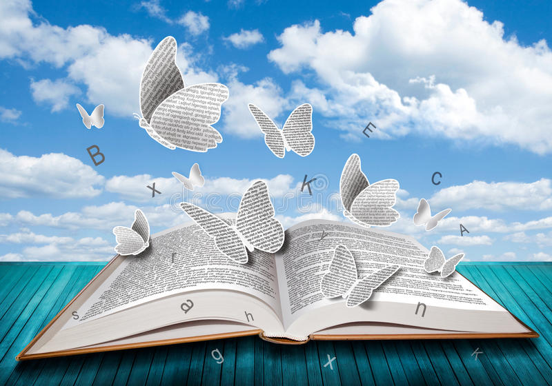 Open book with butterflies letters on blue sky stock images
