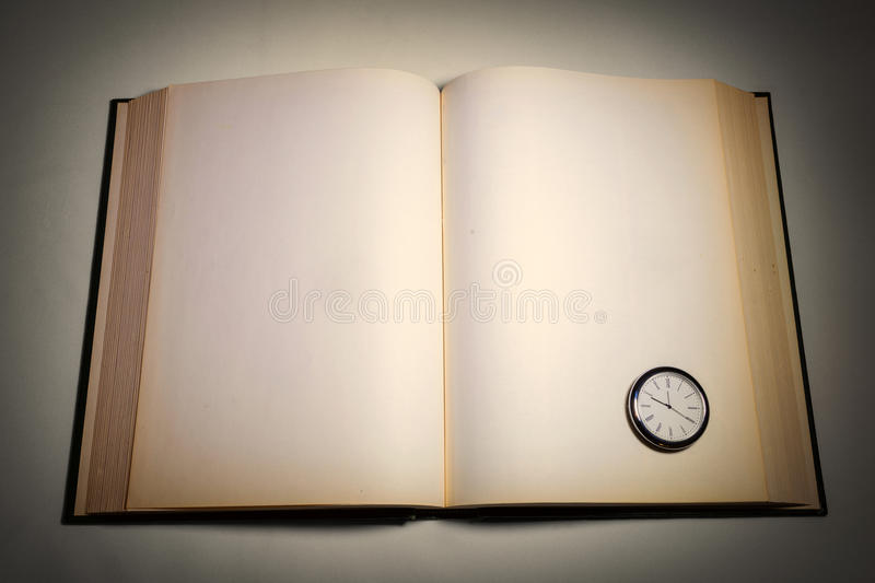 An open book and clock stock images
