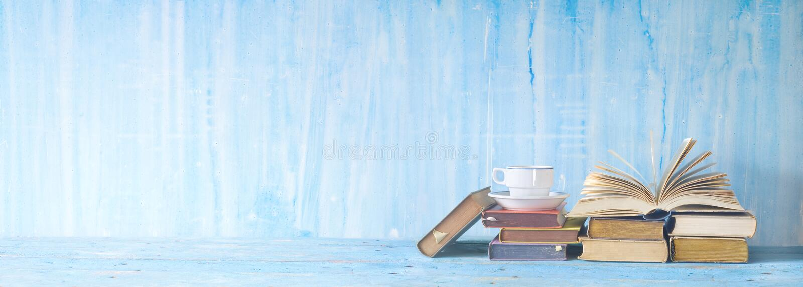 Open book, cup of coffee,reading, literature, education. Open book, cup of coffee on blue grungy background, panoramic, copy space. Reading, literature stock photo
