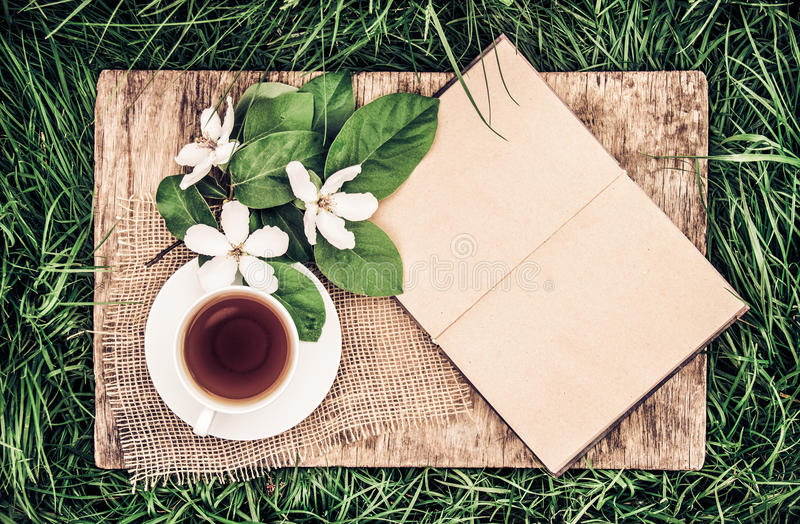 An open book with empty pages, a cup of hot tea and a quince flower. Vintage tinting. Breakfast in the garden. Tea on the green gr royalty free stock photo