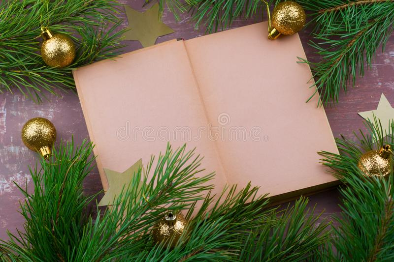 Open book with empty paper sheets and fir green branches with christmas golden balls. Top view brown shabby background stock images