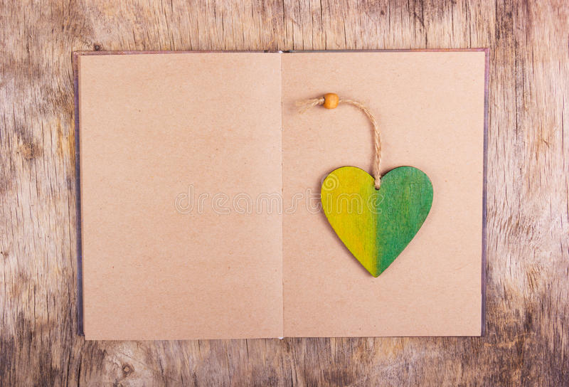 An open book with empty sheets and a wooden bookmark. Wooden pendant in the shape of heart. Copy space royalty free stock photos