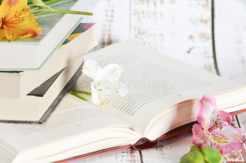 Open book and flowers lay on wooden table stock images