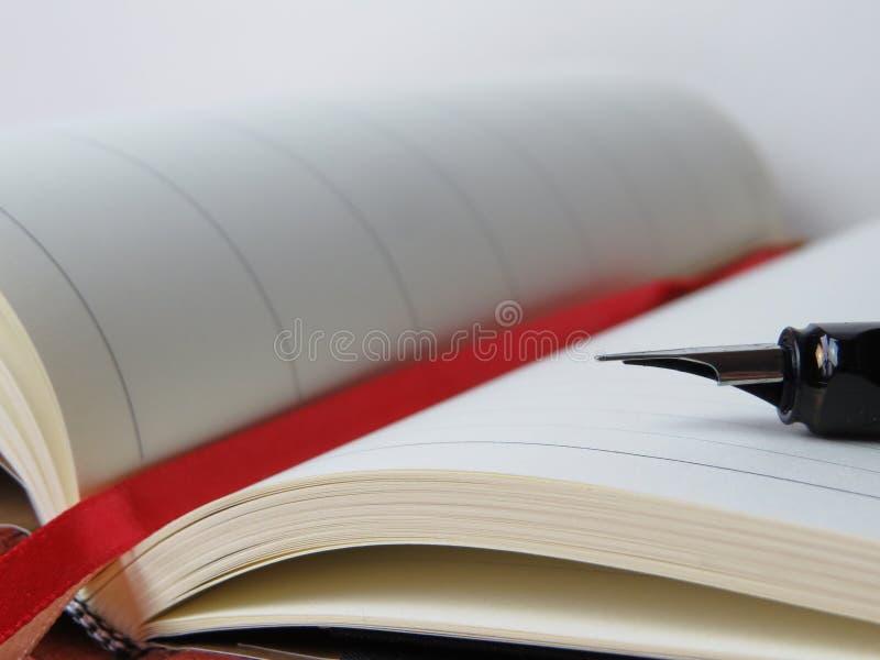 Open book with fountain pen stock photos