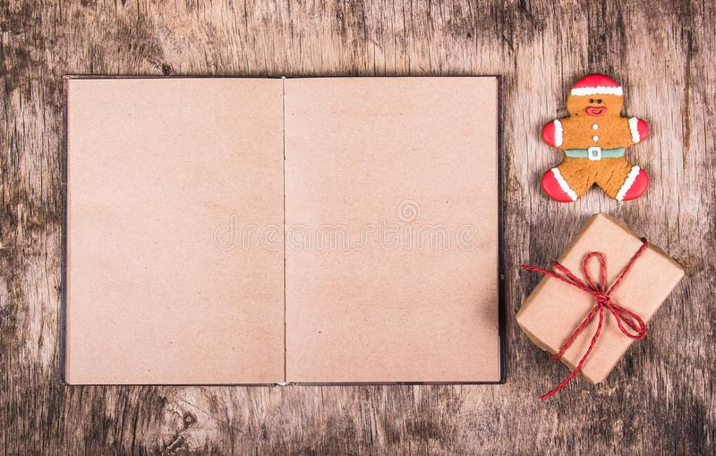 Open book, gingerbread man and gift box. Christmas surprise. Festive backgrounds. stock images