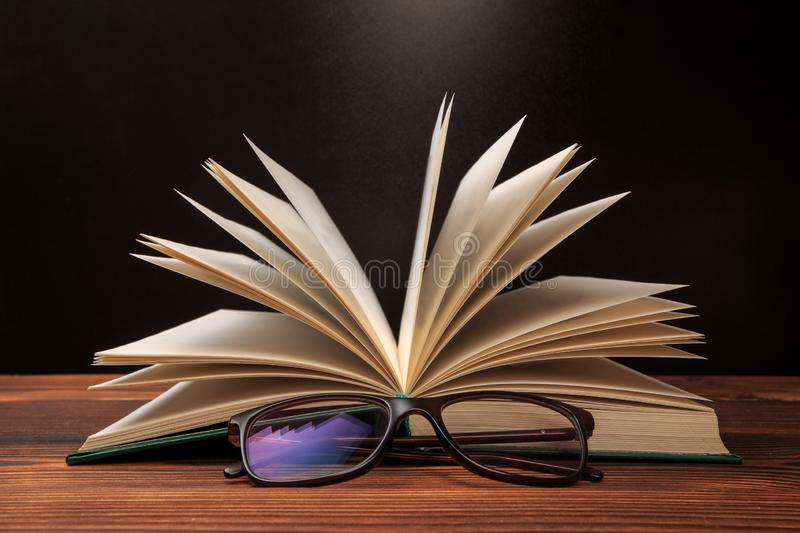 Open book with glasses on black  background stock images