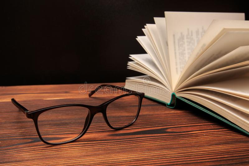 Open book with glasses on black  background royalty free stock images