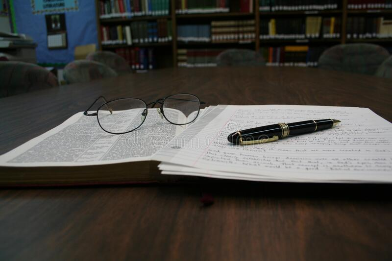 Open book with glasses and pen stock photography