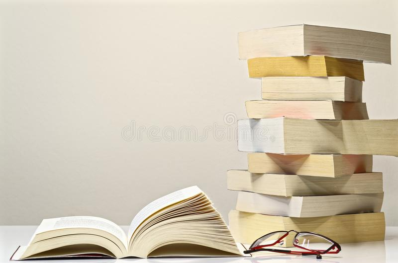 Open book, glasses and pile of books on the white table. With light grey background stock image