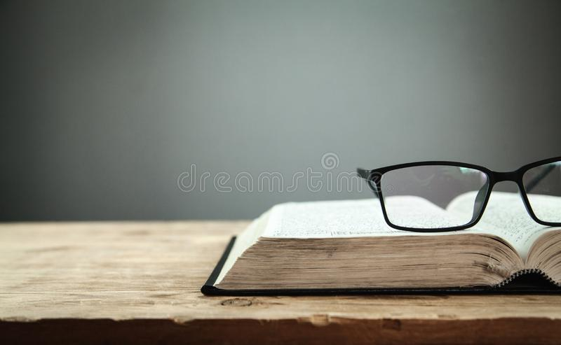 Open book and glasses on the wooden table royalty free stock photos