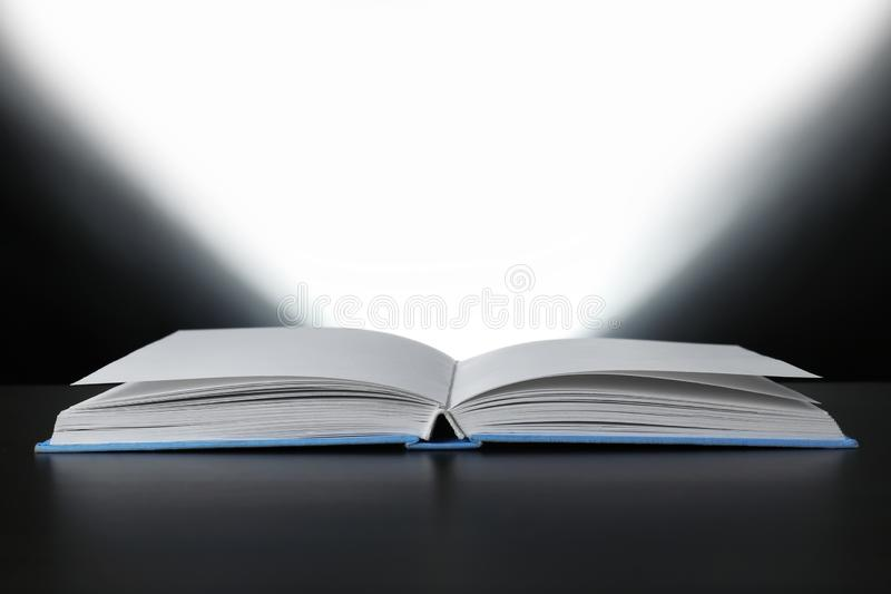 Open book with glowing on dark background royalty free stock photography