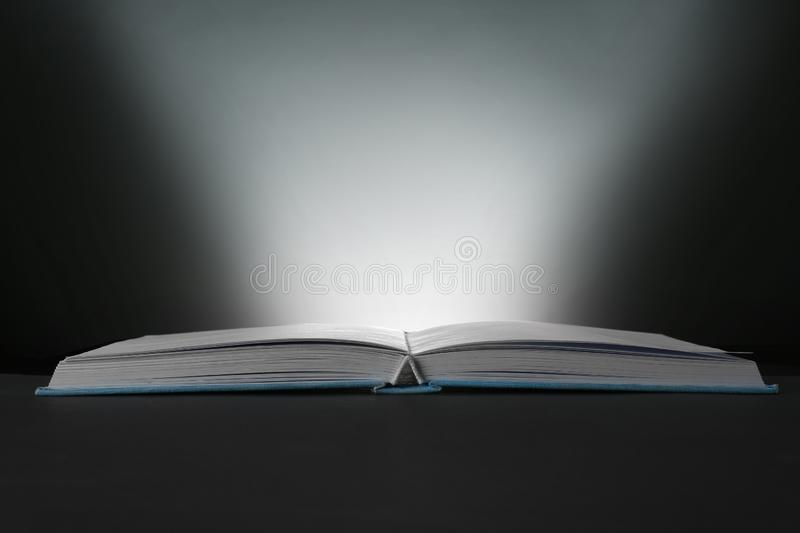 Open book with glowing on dark background stock photos