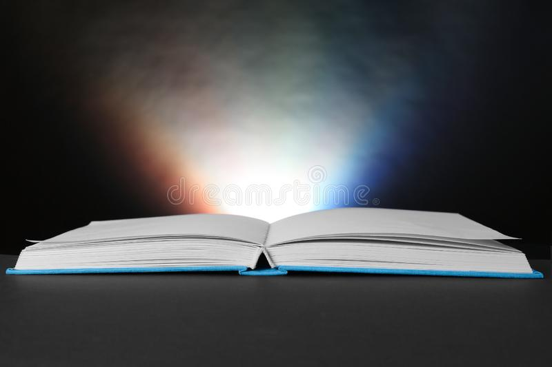 Open book with glowing on dark background royalty free stock photo