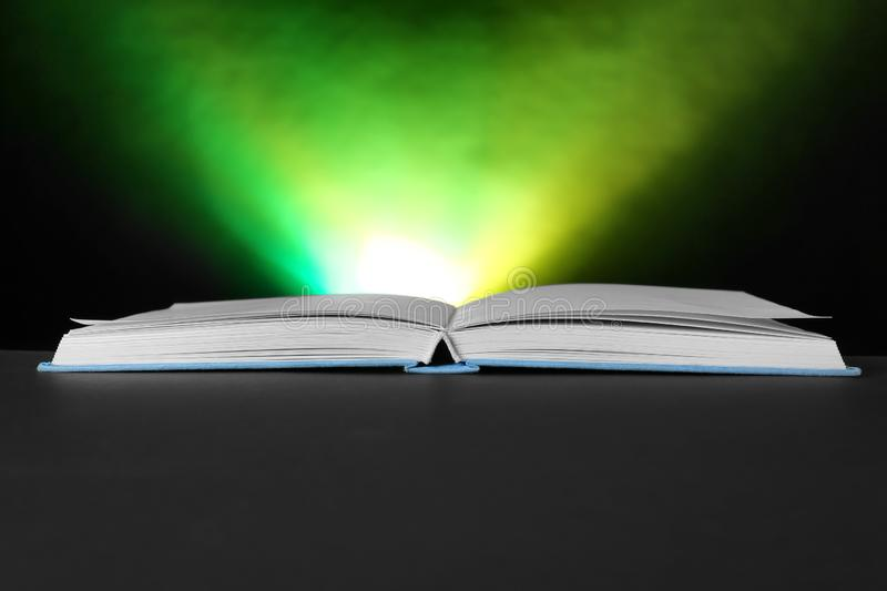 Open book with glowing on dark background royalty free stock images