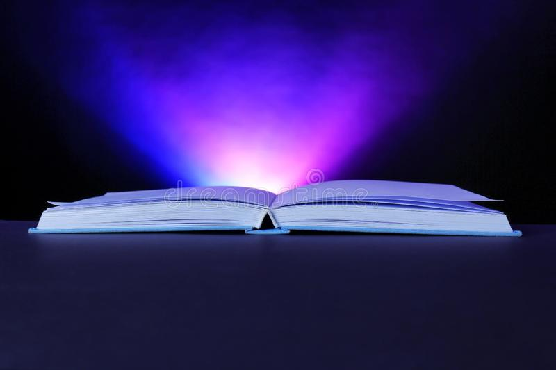 Open book with glowing on dark background stock photography