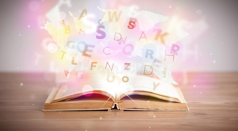 Open book with glowing letters on concrete background. Colorful education concept stock photography