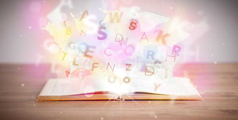 Open book with glowing letters on concrete background. Colorful education concept royalty free stock images