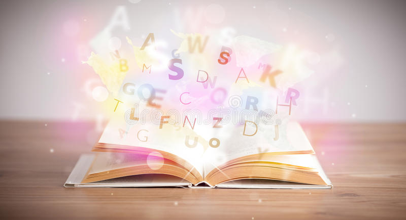 Open book with glowing letters on concrete background. Colorful education concept stock photos