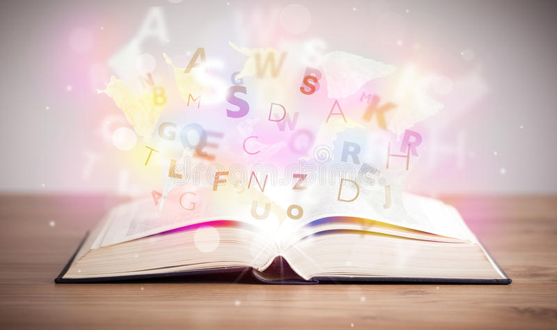 Open book with glowing letters on concrete background. Colorful education concept royalty free stock image