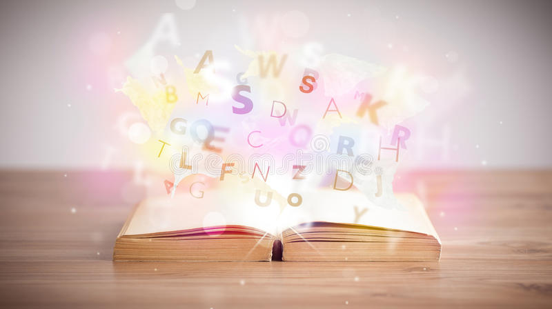 Open book with glowing letters on concrete background. Colorful education concept royalty free stock photography