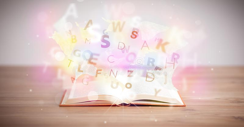 Open book with glowing letters on concrete background. Colorful education concept stock images