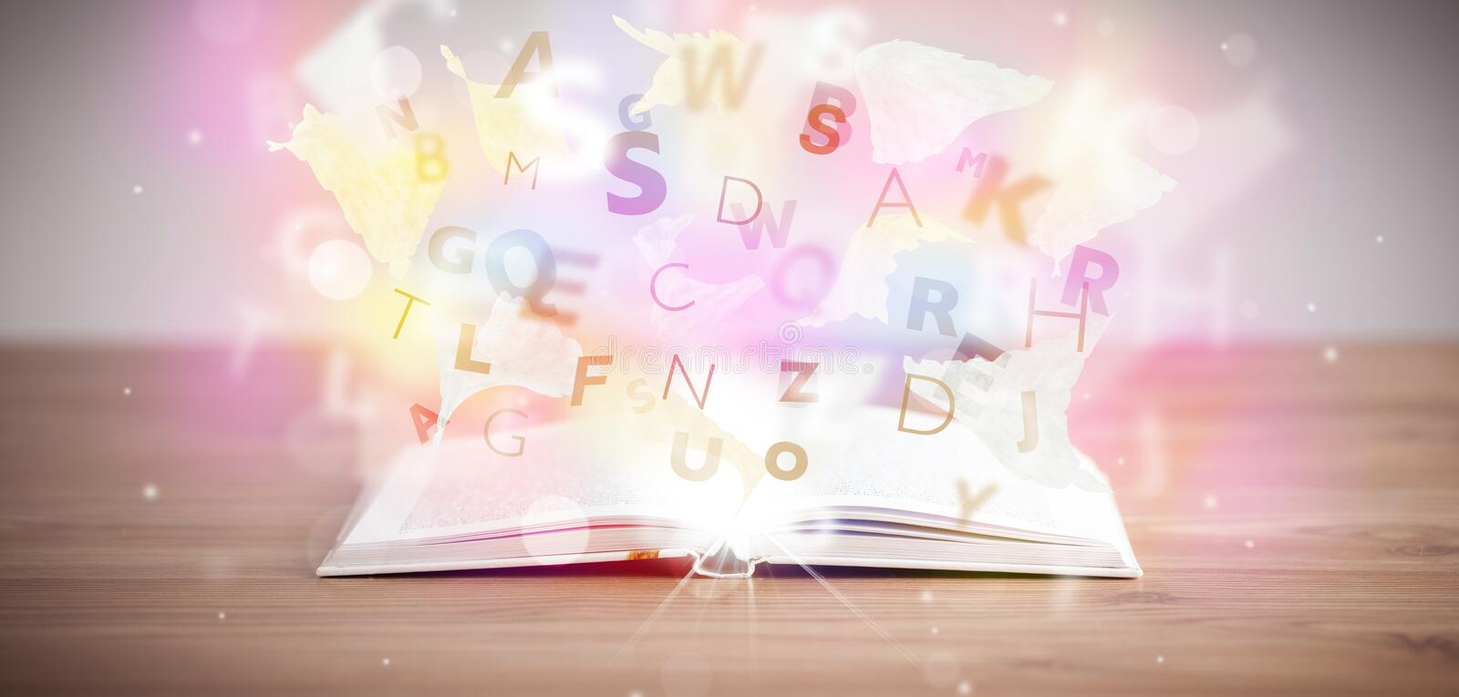 Open book with glowing letters on concrete background. Colorful education concept royalty free stock photo