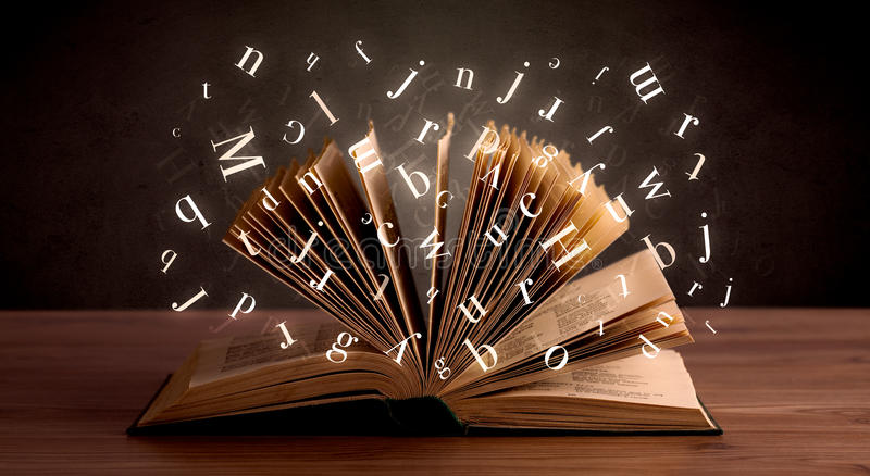 Open book. With glowing letters flying out stock photo