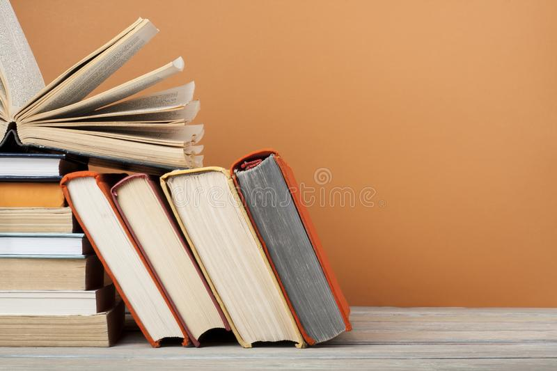 Open book, hardback books on wooden table and colorful wall .Education background. Back to school. Copy space for text. stock photo