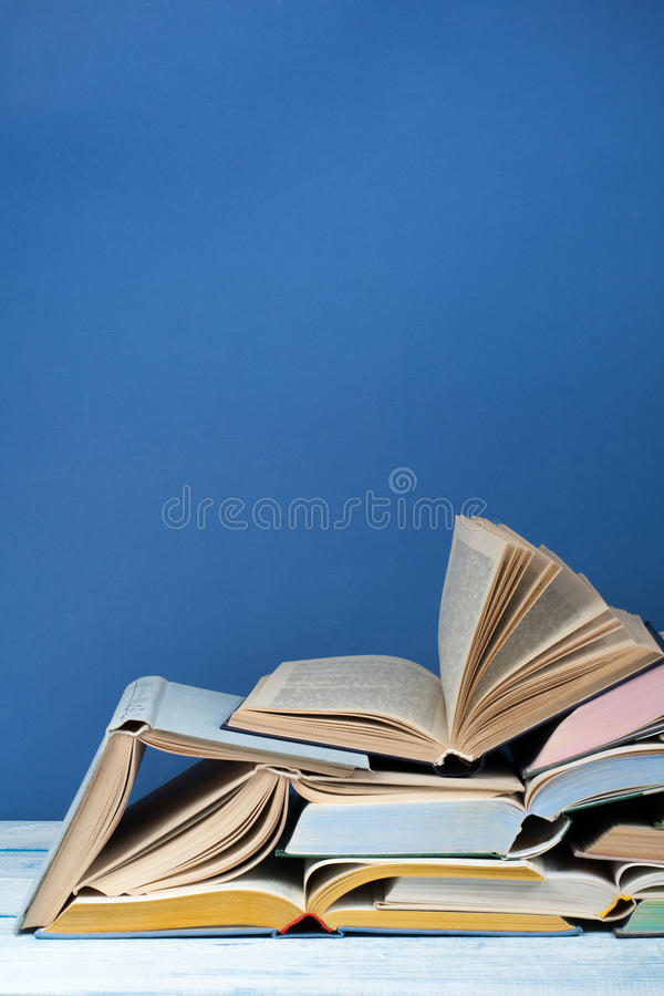 Open book, hardback colorful books on wooden table, blue background. Back to school. Copy space for text. Education royalty free stock image