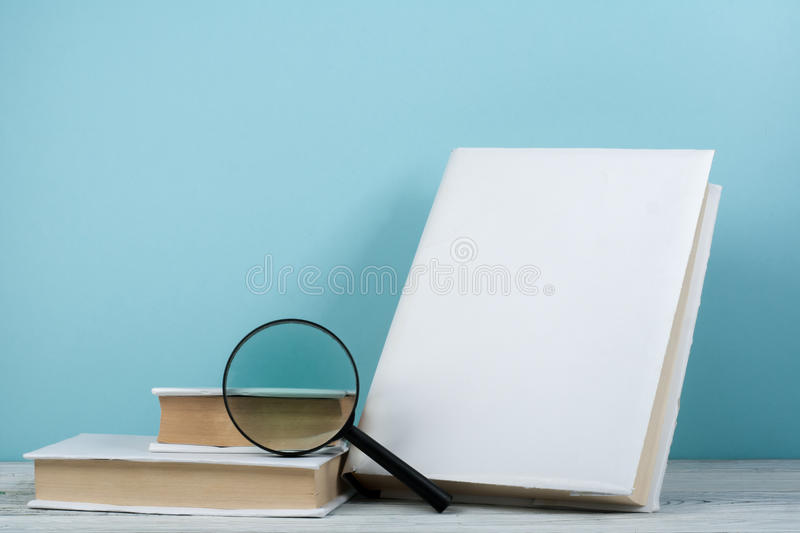 Open book, hardback colorful books on wooden table. Magnifier. Back to school. Copy space for text. Education business stock image