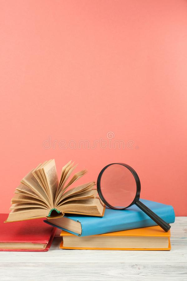 Open book, hardback colorful books on wooden table. Magnifier. Back to school. Copy space for text. Education business stock images