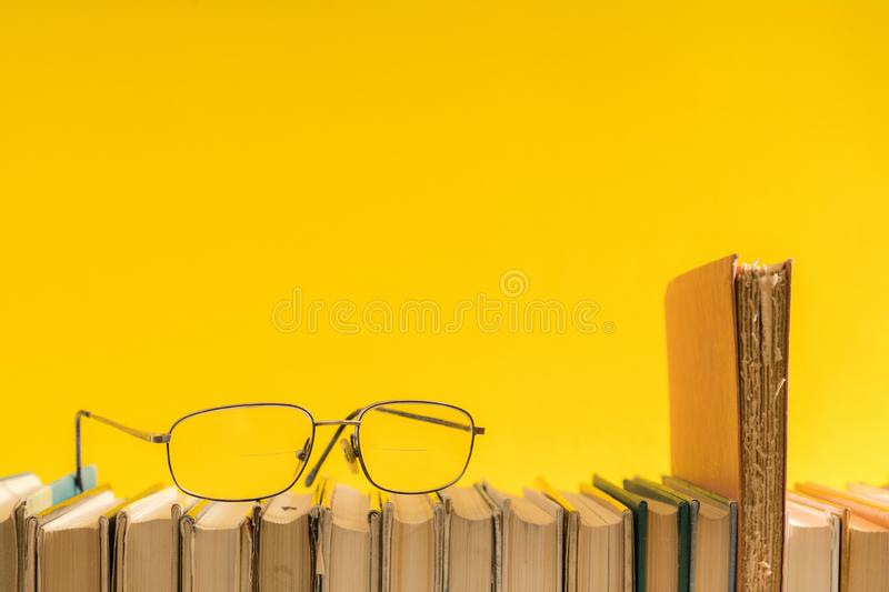 Open book, hardback hard cover colorful books with reading glass. Es on the side. Back to school. Copy space for text. Education, studying, learning, business royalty free stock photography